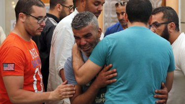 Tahar Mejri is comforted by friends after carrying the coffin of his 4-year-old son, Kylan, at the ar-Rahma mosque in Nice. Tahar's wife, Olfa Kalfallah, was also killed.