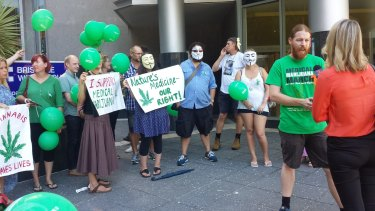 Supporters for a man who allegedly gave his sick daughter cannabis oil stand outside Brisbane Magistrates Court.