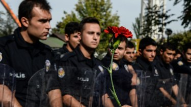 A protester holds a carnation as police block the route to the site of the Ankara explosions.