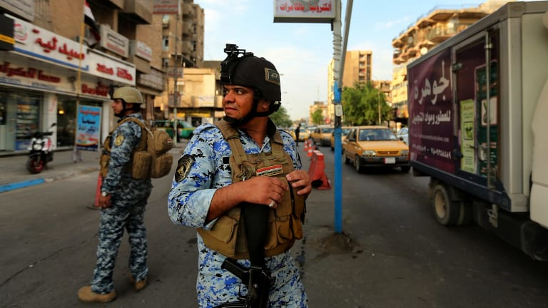 Nervous state: On a day when six bombs went off in the city, Iraqi policemen patrol Baghdad's Karrada district.