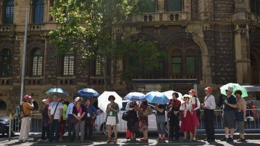 Tourists shield themselves from the hot weather under umbrellas as they wait for a tram on LaTrobe Street in the CBD on March 8.