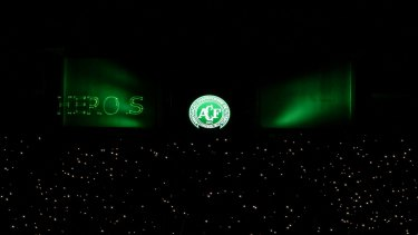 """Mobile phone flashlights are used by fans to pay tribute to Chapecoense Real players killed in Monday's plane crash in Colombia. In green, the word """"herois"""" (heroes) is misspelt by a lighting malfunction."""