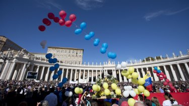 Balloons fly as Pope Francis delivers his Angelus prayer from the studio window overlooking St Peter's Square on Sunday.