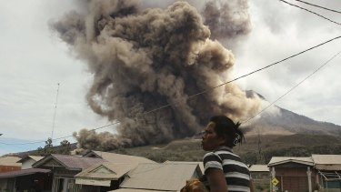 A resident looks on as Mount Sinabung erupts, as seen from Sukanalu village, North Sumatra.