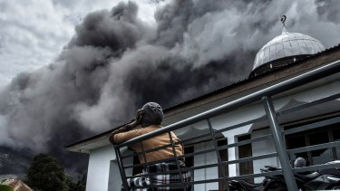 An Indonesian woman looks on as Mount Sinabung spews ash.
