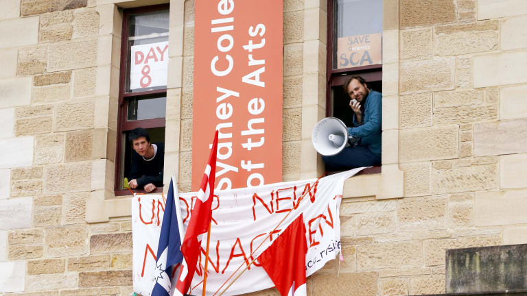 Students are seen from the windows of the administration offices of the Sydney College of Arts before they were removed.