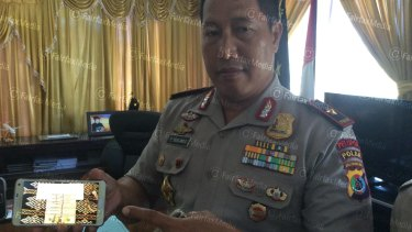General Endang Sunjaya, police chief of East Nusa Tenggara province, shows a mobile phone with a picture of the money allegedly paid to people smugglers by Australia in June this year.