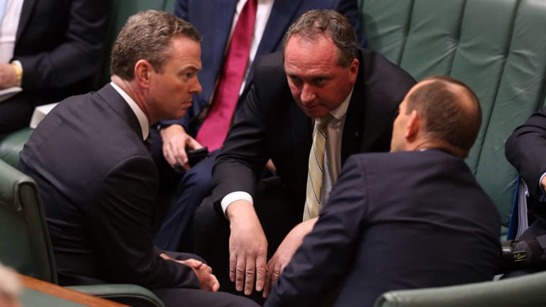 Agriculture Minister Barnaby Joyce consults with leader of the house Christopher Pyne and Prime Minister Tony Abbott during question time on Monday.
