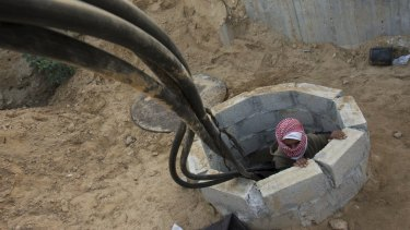 A Palestinian smuggler climbs from a tunnel alongside a hose used to bring fuel from Egypt to Gaza in 2008.