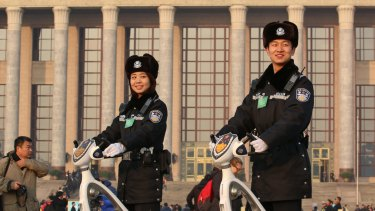 Security guards patrol Tiananmen Square during the National People's Congress. Beijing knows that carefully choreographed set pieces for traditional media may fall flat with China's youth.