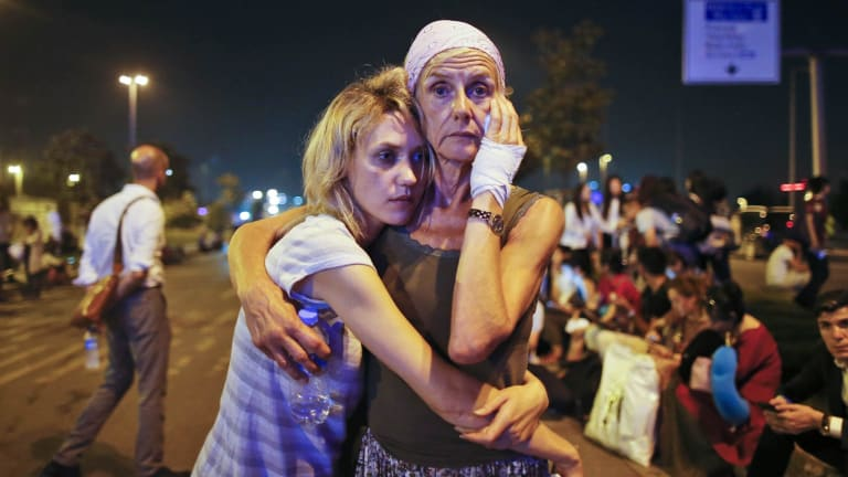 Passengers embrace as they wait outside Istanbul's Ataturk airport, following their evacuation after the attack.
