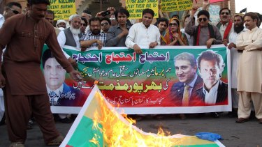An activist of Pakistan Tehreek e Insaaf party torches a Myanmar flag during a protest in support of Rohingya Muslims in Multan on Monday.