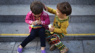 Young migrant children play as they wait to board a train to Austria at Keleti station in Budapest on Monday.