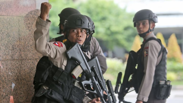 A police officer gives a hand signal to a squad mate as they search a building near the site of an explosion in Jakarta, Indonesia on Thursday.