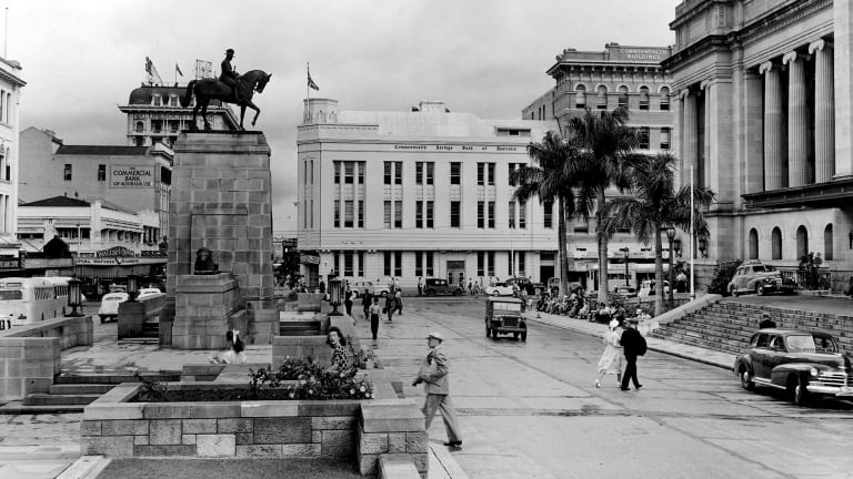 A historic photo of King George square, Brisbane, where an equestrian statue of the late King George V faces the entrance to the city hall. The memorial is surrounded with garden plots and fountains.