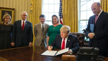 US President Donald Trump signs an executive order calling for a rewriting of major provisions of the 2010 Dodd-Frank Act.