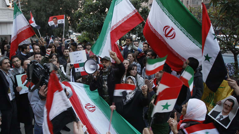 Pro-Syrian government protesters shout slogans and wave Iranian and Syrian flags in front the Iranian embassy to thank Iran for its support of the Syrian government.