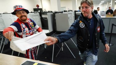 John Olsen, of Ankeny, Iowa, left, and Mark Cooper, of Des Moines, Iowa, race to be the first to submit their ballot in Des Moines.