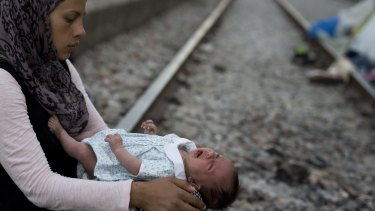Rajad, 19, from Syria, holds her 42-day-old baby girl Yasmin at a makeshift refugee camp at the northern Greek border point of Idomeni on Friday.