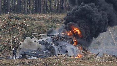 The surviving pilot stands near the burning wreckage.