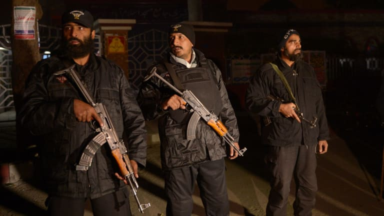 Pakistani commandos stand guard during a rally for the 140 victims of the shooting in Peshawar.
