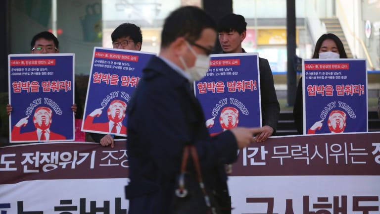 A man walks past a group of South Koreans protesting against US President Donald Trump near the US embassy in Seoul on Wednesday.