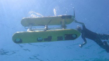 An autonomous underwater vehicle preparing to take high-res images of a coral reef.