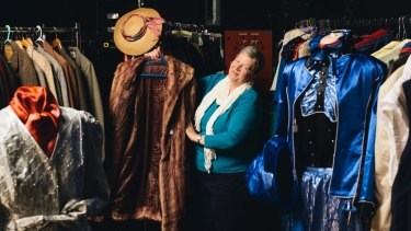 Canberra Repertory Society's Liz de Totth with some of the vintage clothes on sale as part of the society's 85th birthday celebrations.