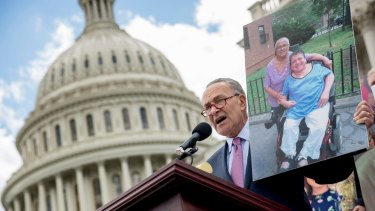 Democratic Senator Chuck Schumer holds up a photograph of constituents who would be adversely affected by the healthcare bill at a rally on Tuesday.