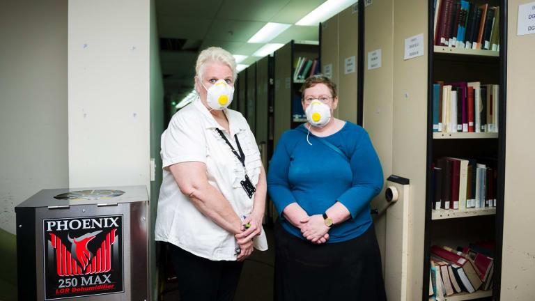 Senior archivist Sarah Lethbridge, left, and university librarian Roxanne Missingham survey the damage after last weekend's floods.