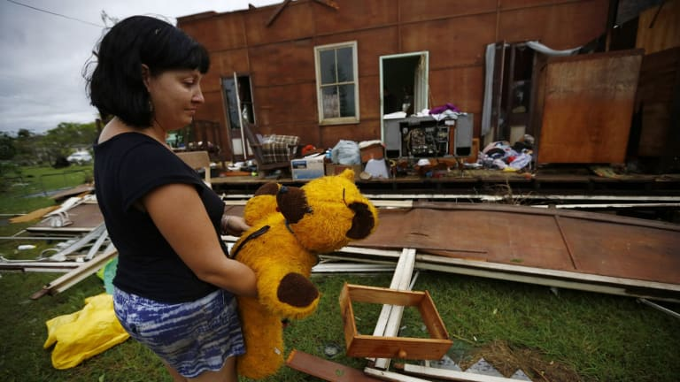 Melanie Cobb holds her childhood teddy bear she retrieved from her grandmother's damaged home after Cyclone Marcia hit the coastal town of Yeppoon.