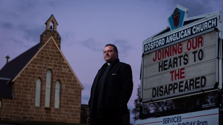 Anglican priest Father Rod Bower with the sign in front of his Gosford church which frequently features messages critical of immigration and asylum seeker policy. 7 July 2014 Photograph by Jon Reid