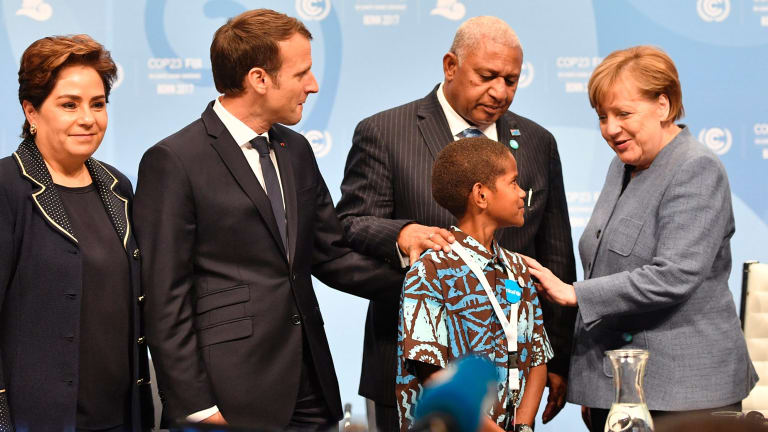 German Chancellor Angela Merkel and world leaders, with Fijian child Timoci Naulusala at the United Nations climate change talks in Bonn