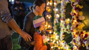 A young girl is guided to place a candle on a flower wall.
