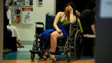 Intoxicated woman waits for treatment  in the waiting room of the emergency department at Calvary Hospital on her ankle after falling off her bicycle