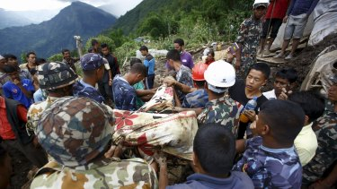 Rescue team members from the Nepalese Army retrieve the body of a landslide victim at Lumle village near the Annapurna Circuit.