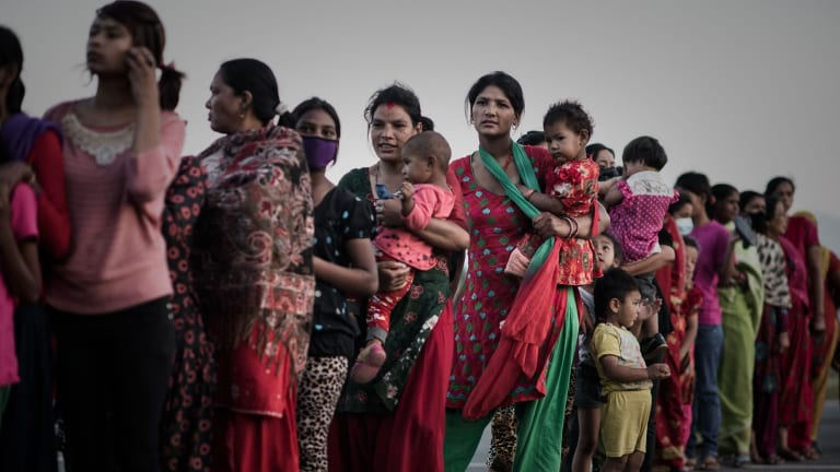 Earthquake survivors queue for relief food at an open ground shelter in Kathmandu on Tuesday.