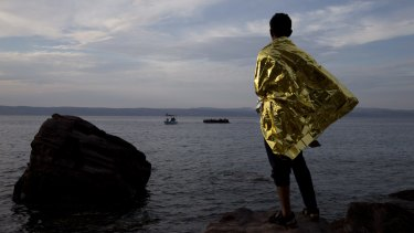 A refugee wrapped in a thermal blanket looks as a dinghy full of migrants approaches the coast of Lesbos.