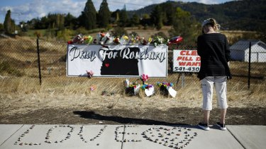 A woman visits a makeshift memorial near the road leading to Umpqua Community College in Roseberg after the mass shooting there.