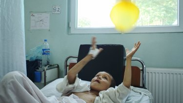 A young patient, recovering from a severe shrapnel wound, playing with a balloon.