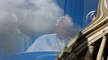 Pope Francis sits on a bus as the Vatican's Bernini colonnade is reflected on the windscreen on Sunday.