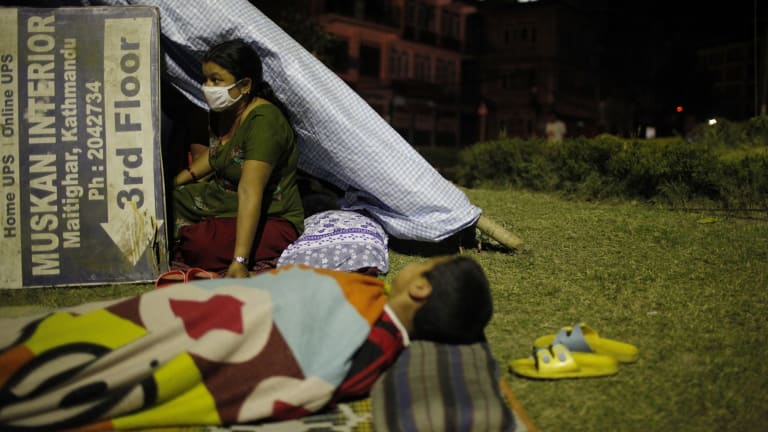 A Nepalese woman sits inside her makeshift tent in an open space in Kathamandu, Nepal after a second quake struck.