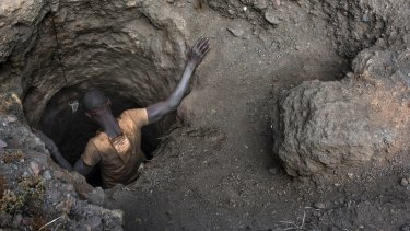 """A """"creuseur"""" descends into a tunnel at the mine in Kawama. About 100,000 cobalt miners in Congo use hand tools to dig hundreds of feet underground with little oversight and few safety measures, according to workers, government officials and evidence found."""