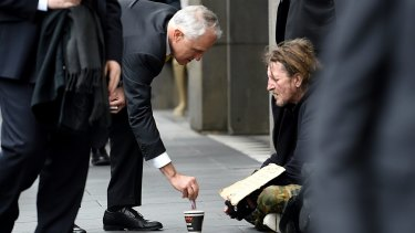 Prime Minister Malcolm Turnbull gives a homeless man five dollars. An elite group with incomes above $1 million give more than one fifth of all donations.