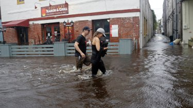 Residents walk along flooded Water Street in Wilmington, North Carolina.
