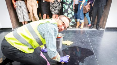Adam Bandt cleaning the floor of ACCA as part of artist Nat Thomas installation <i>Man Cleaning Up</i>.