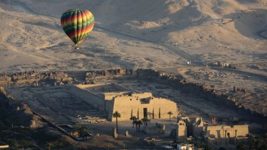 A hot air balloon flying over an ancient temple on the west bank of the Nile River in Luxor, Egypt, 2016.
