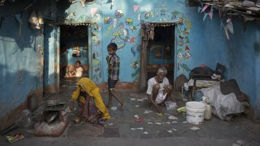 Sitting outside their Rajasthani home a family prepares a meal at dusk. The family's home is inside a small slum in Vasant Vihar, an exclusive suburb of New Delhi, India.