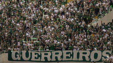 """Supporters of Brazil's Chapecoense gather for a memorial for the players who died in a plane crash in Colombia, at Arena Condado stadium in Chapeco, Brazil, on November 30. The banner reads """"warriors""""."""