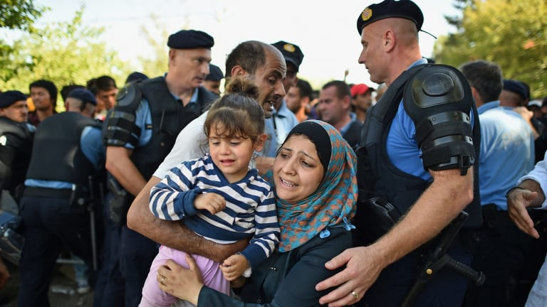 A migrant mother carries her daughter in her arms as she and other migrants force their way through police lines at Tovarnik station for a train to take them to Zagreb.